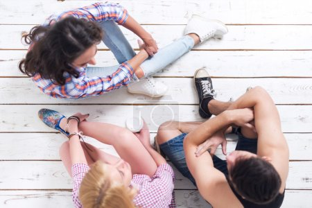 Photo for Friends two girls and guy sitting on floor in summer jeanswear street urban casual style talking, having fun, top view - Royalty Free Image