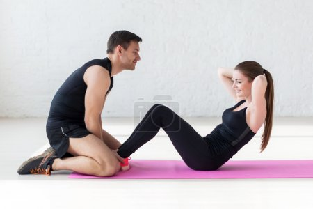 Woman doing abdominal crunches press exercise on the mat with her sports male trainer in gym side view concept sport, fitness, lifestyle and people