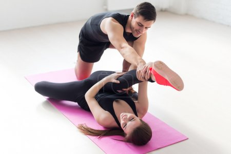 woman lying on mat lifting leg up doind exercise for flexible male trainer helping her concept sport health fitness aerobics gymnastic
