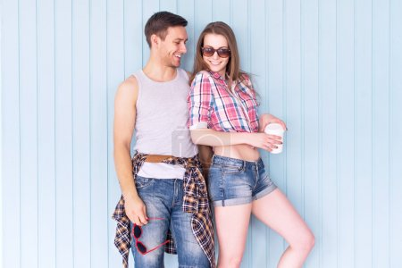 Photo for Happy couple friends wearing sunglasses in summer jeanswear street urban casual style talking having fun standing near wall - Royalty Free Image