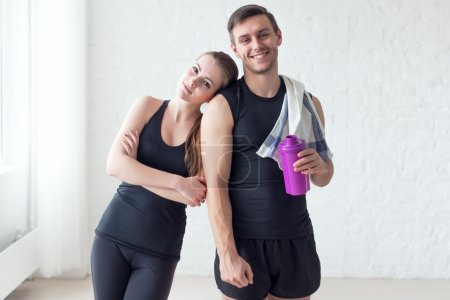 Portrait sportive couple athletic man and woman after doing exercises sportsman towel on shoulder holding shaker protein cocktail or bottle with water