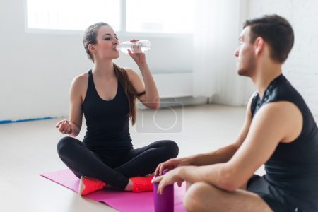 Sport connecting people friends relaxing after workout girl drinking water and man Side view of young couple in sports clothing sitting talking conversing.