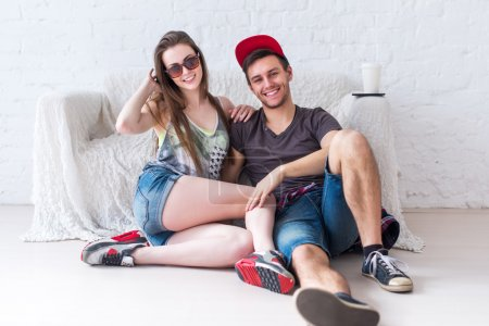 Friends girl and guy sitting on floor at home in summer jeanswear street urban casual style talking, having fun