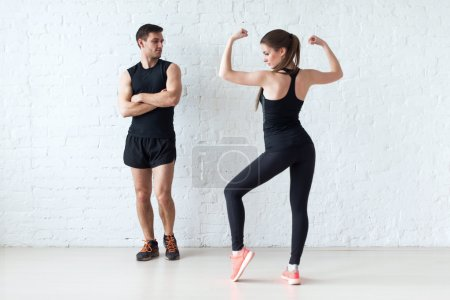 sportive couple athletic woman posing and showing muscles focus on man.