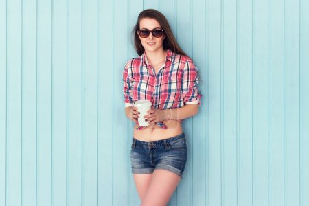 Outdoor summer closeup portrait of young stylish woman in shirt and denim shorts sunglasses holding paper cup coffee standing on the blue background