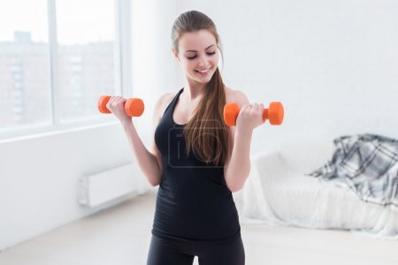 Active sportive athletic woman with dumbbells pumping up muscles biceps concept fitness sport training lifestyle.