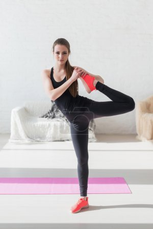 Girl working stretching leg muscles warm up at home fitness, sport, training and lifestyle concept.