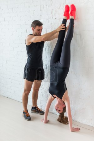 woman sportsman doing a handstand against concrete wall male trainer helping her concept sport, fitness, lifestyle and people