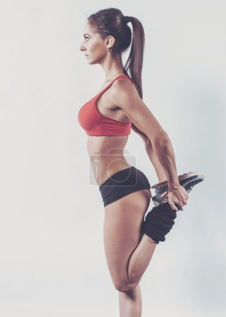 Portrait of muscular active athlete woman standing looking forward leg in hands doing exercise warming up working stretching with fitness, sport, training and lifestyle concept