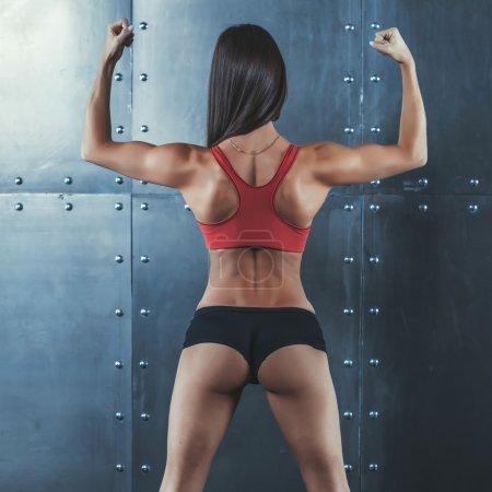 Muscular active athletic young woman with sexy buttocks showing muscles of the back shoulders and hands fitness, sport, training lifestyle concept.