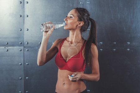 Muscular sporty athlete woman drinking water at the gym after exercising working out fitness, sport, training and lifestyle concept.
