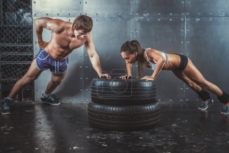 Sportswomen. Fit sporty woman and man doing push ups on tire strength power training concept crossfit fitness workout sport lifestyle.