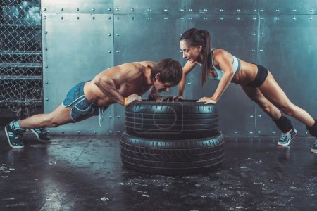 Photo for Sportswoman. Fit sporty woman doing push ups on tire strength power training concept crossfit fitness workout sport and lifestyle - Royalty Free Image