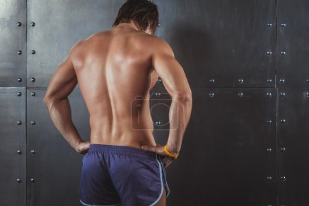 Athletic young man showing muscles of back Rear view strong male. Fitness male model standing near wall healthy lifestyle bodybuilding concept