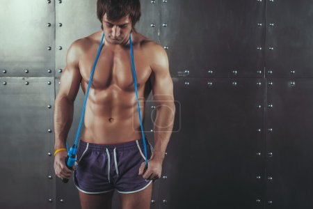 Fitness model muscular man with skipping jumping rope around his neck copy space healthy lifestyle bodybuilding concept.