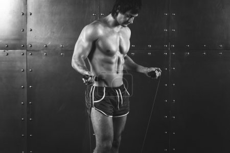 Fitness model muscular man with skipping jumping rope around his neck copy space healthy lifestyle bodybuilding concept black and white
