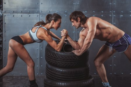 Athlete muscular sportsmen man and woman with hand...