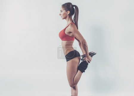 Muscular active athlete woman standing looking forward leg in hands doing exercise warming up working stretching with copy space fitness, sport, training and lifestyle concept.