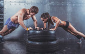 Sportsmen. Fit sporty woman and man doing push ups on tire strength power training concept crossfit fitness workout sport lifestyle.