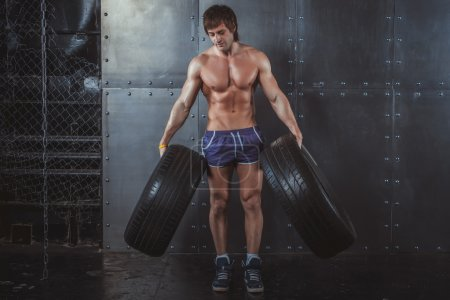 Sportsman athlete crossfit man working out exercising with a tires powerlifting healthy lifestyle bodybuilding concept.