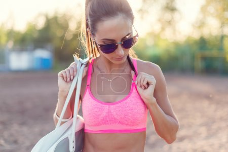 Attractive fit woman in sportswear training outdoors, female athlete with perfect body resting after workout, fashion sport model healthy lifestyle