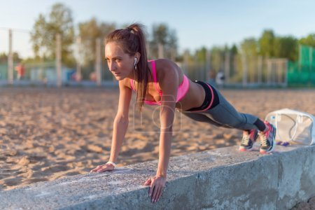 Fitness woman doing push ups Outdoor training workout summer evening. Concept sport healthy lifestyle.
