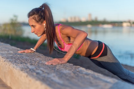 Fitness woman doing push ups Outdoor training workout summer evening side view Concept sport healthy lifestyle.