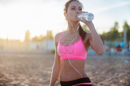 Photo for Beautiful fitness athlete woman resting drinking water after work out exercising on beach summer evening in sunny sunshine outdoor portrait. - Royalty Free Image