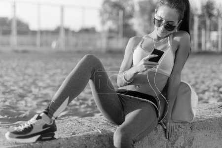 Photo for Beautiful fitness athlete woman wearing sunglasses resting listening music after work out exercising on summer evening in beach at sunset with smartphone outdoor portrait - Royalty Free Image