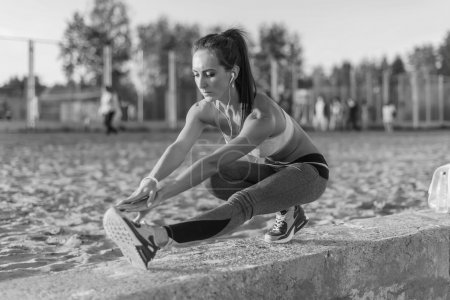 Photo for Athletic woman stretching her hamstring, legs exercise training fitness before workout outside on a beach at summer evening with headphones listening music - Royalty Free Image
