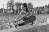 Sportliche Frau, dehnen ihre Oberschenkel, Beine Übung training Fitness vor Training außerhalb an einem Strand am Sommerabend mit Kopfhörer Musik hören