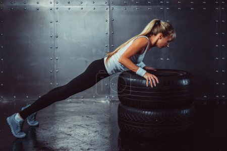 Sportswoman. Fit sporty athlete woman doing push ups on tire strength power training concept crossfit fitness workout sport and lifestyle side view