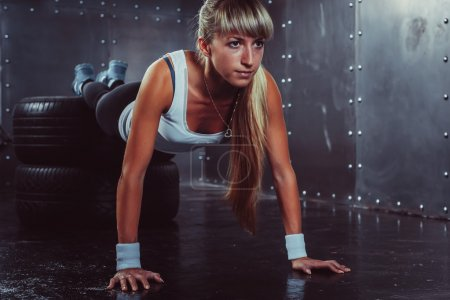 sporty athlete woman doing push ups on tire strength power training concept cross fit fitness workout sport and lifestyle
