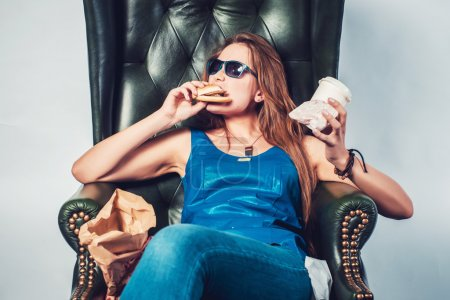 Photo for Funny crazy woman eating hamburger junk food and fries sitting in chair - Royalty Free Image