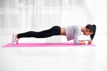 Slim fit girl doing planking core muscles exercise indoors at home in the living room side view fitness healthy lifestyle and diet concept