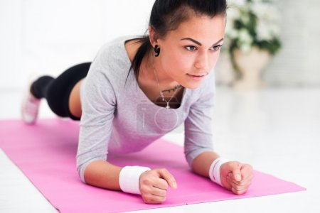 Pretty young woman doing plank abdominal exercise at home in white room concept healthy lifestyle sport fitness