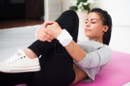 Fit woman doing aerobics gymnastics stretching exercises her leg lying on back warm up at home yoga mat.