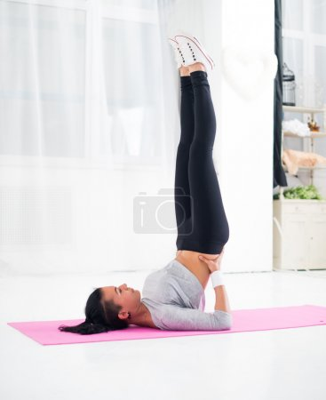 Fit woman doing shoulder stand on mat practising yoga health and fitness concept