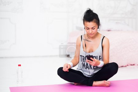 Woman in headphones looking at smartphone listening music relaxing after training