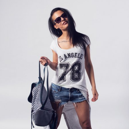 Young sexy happy woman looking at camera wearing sunglasses. Portrait of trendy girl having fun style casual concept lifestyle urban fashion.