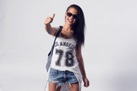 Young woman in sunglasses showing thumb up looking at camera. Portrait of trendy girl having fun style casual concept lifestyle urban fashion