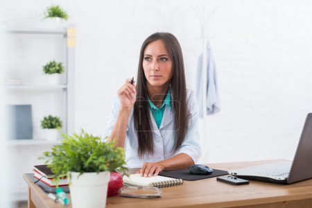 Portrait of physician doctor working in medical office workplace sitting at desk.