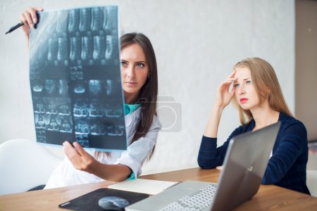 Woman doctor and patient looking at the x-ray or MRI picture in hospital.