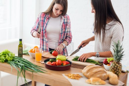 Two girls friends preparing dinner in a kitchen concept cooking, culinary, healthy lifestyle.
