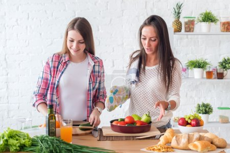 Two girls preparing dinner in a kitchen concept cooking, culinary, healthy lifestyle.