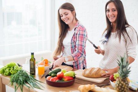 Women preparing dinner in a kitchen concept dietin...