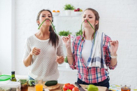 Photo for Women preparing healthy food playing with vegetables in kitchen having fun concept dieting nutrition. - Royalty Free Image