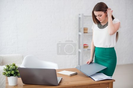 business woman at office standing near table with documents.