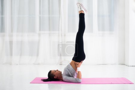 Fit woman doing shoulder stand