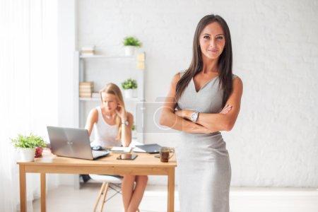 Photo pour Portrait de femme d'affaires avec les bras croisés et souriant dans un bureau - image libre de droit